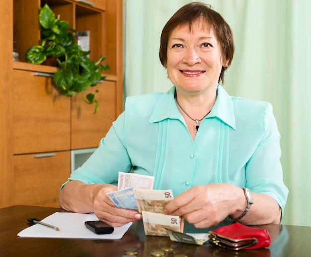 Portret van gelukkige vrouwelijke gepensioneerde met contant geld en rekeningen