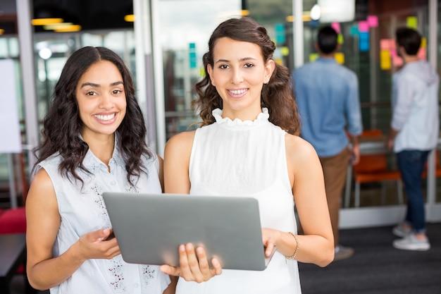 Portret van gelukkige vrouwelijke leidinggevenden die laptop met behulp van