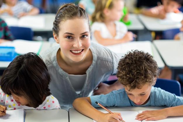 Portret van gelukkige vrouwelijke leraar die schoolkinderen helpt