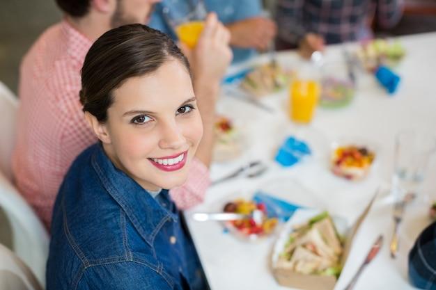 Portret van gelukkige vrouwelijke stafmedewerker die ontbijt heeft