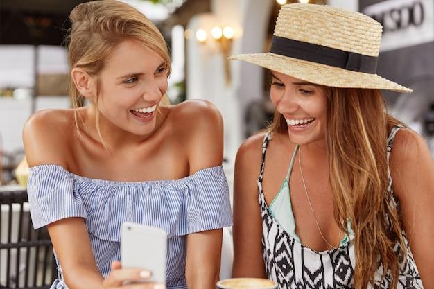 Portret van gelukkige vrouwen gekleed in stijlvolle zomerkleding, lacht vreugdevol als grappige foto kijken op mobiele telefoon,