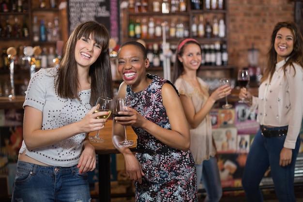 Portret van gelukkige wijfjesvrienden die wijnglazen houden