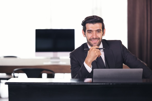 Portret van gelukkige zakenman achter bureau