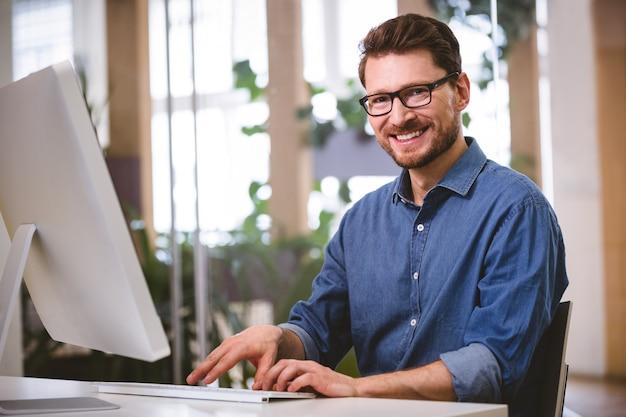 Portret van gelukkige zakenman die aan computer op creatief kantoor werken