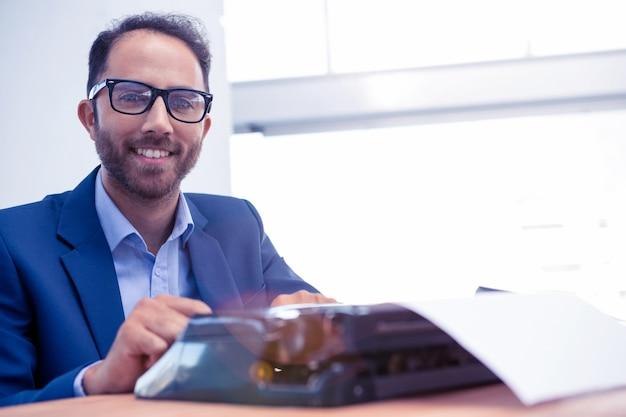 Portret van gelukkige zakenman die aan schrijfmachine werkt terwijl het zitten in helder bureau