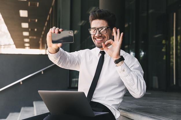 Portret van gelukkige zakenman gekleed in formeel pak buiten glazen gebouw met laptop zitten en selfie foto op mobiele telefoon