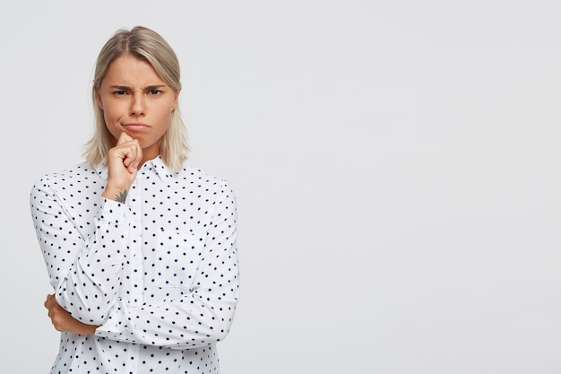 Portret van gelukkige zelfverzekerde blonde jonge vrouw draagt polka dot shirt glimlachend en wijst naar de zijkant door vinger geïsoleerd over witte muur