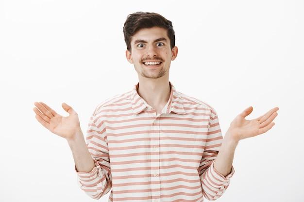 Portret van gelukkige zorgeloze aantrekkelijke mannelijke collega in gestreept overhemd, gespreide handpalmen omhoog en breed glimlachend, positieve en vriendelijke houding uitend, niet onder de indruk en onverschillig voor de situatie