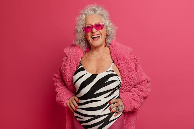 Portret van gelukkige zorgeloze rijpe vrouw heeft een goed humeur, geniet van het leven, heeft een aangenaam vrolijk gesprek, draagt trendy zonnebril, vormt tegen roze muur. gepensioneerde dame die buiten gaat wandelen