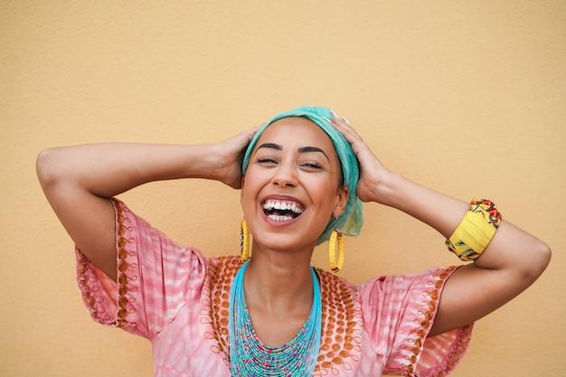 Portret van gelukkige zwarte jonge vrouw in traditionele afrikaanse kleding - focus op gezicht