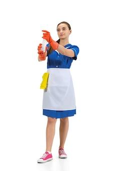 Portret van gemaakte vrouw, dienstmeisje, schoonmaakster in wit en blauw uniform dat over wit wordt geïsoleerd