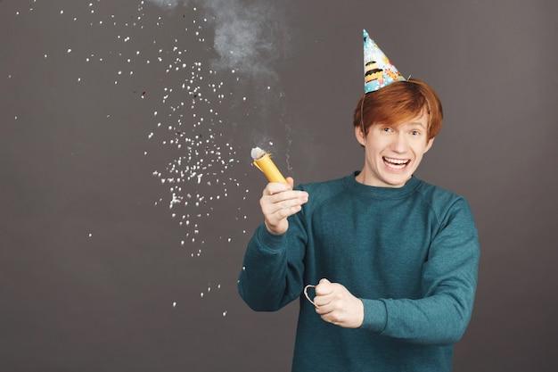 Portret van gember jongen op verjaardag met vrienden doorbrengen in warme en gelukkige sfeer.