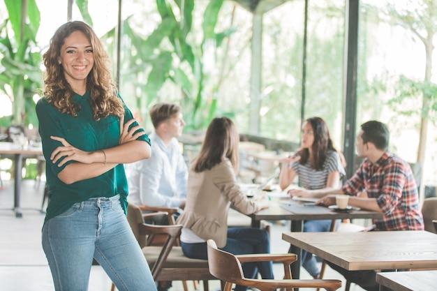 Portret van gemengd ras aantrekkelijke jonge vrouw die lacht tijdens een ontmoeting met haar team in een café