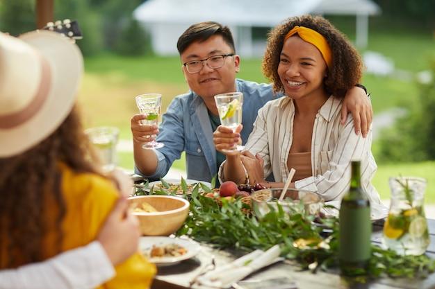 Portret van gemengd ras jong koppel omarmen zittend aan tafel met drankjes en genieten van diner met vrienden buiten op zomerfeest
