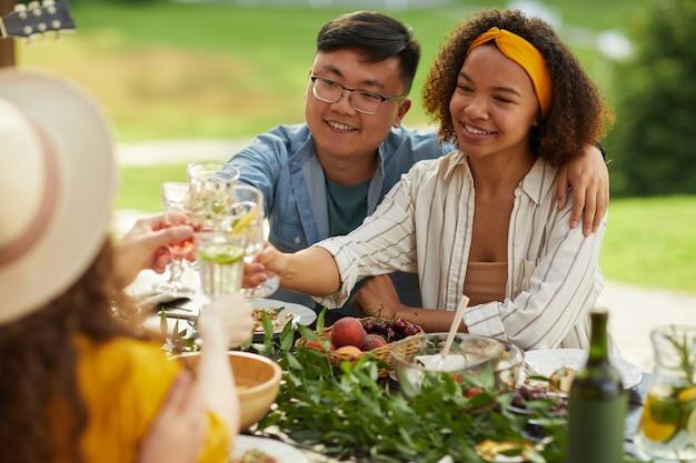 Portret van gemengd ras jong koppel roosteren terwijl u geniet van een diner met vrienden buiten op zomerfeest