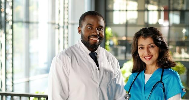 Portret van gemengd ras jonge paar mannelijke en vrouwelijke artsen in uniformen glimlachend vreugdevol naar camera in kliniek. multi-etnische man en vrouw, medici in het ziekenhuis. arts met verpleegkundige doc en assistent