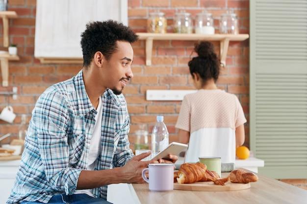 Portret van gemengd ras man draagt geruit overhemd stuurt sms-bericht vanaf zijn digitale tabletcomputer, maakt gebruik van draadloos internet,