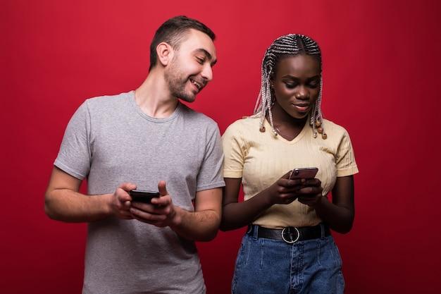 Portret van gemengd ras man en vrouw fronsen en gluren naar elkaars mobiele telefoons geïsoleerd op rode achtergrond