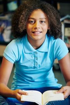 Portret van gemengd ras tienermeisje met krullend haar, zittend op de vloer met geopend boek