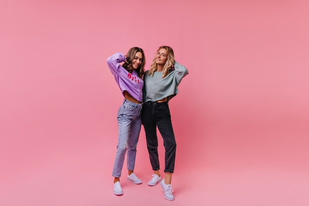 Portret van gemiddelde lengte van aangenaam donkerbruin meisje in spijkerbroek tijd doorbrengen met zus. zorgeloze dames in casual outfit geïsoleerd op pastel.