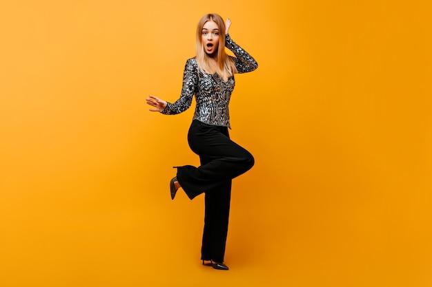 Portret van gemiddelde lengte van aangename vrouw in stijlvolle zwarte broek. portret van verrast glamoureuze vrouw geïsoleerd op oranje