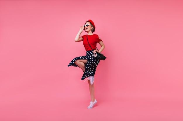 Portret van gemiddelde lengte van aantrekkelijk frans meisje in zwarte rok. stijlvolle jonge vrouw in zonnebril en rode baret dansen.