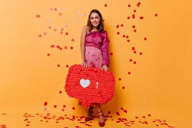 Portret van gemiddelde lengte van aantrekkelijk meisje dat zich op sinaasappel met confettien bevindt. betoverende vrouw in roze jurk met plezier.