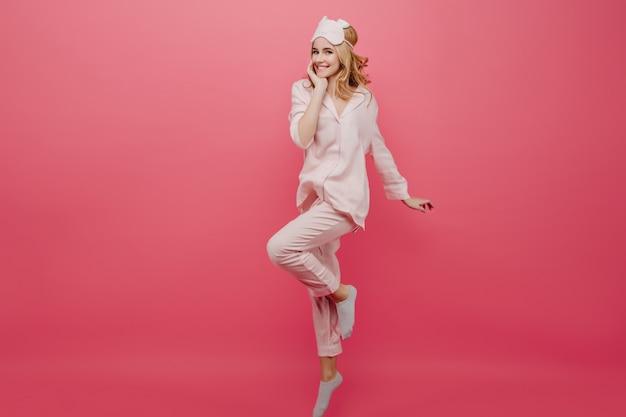 Portret van gemiddelde lengte van aantrekkelijk meisje in pyjama's en sokken die op roze muur dansen. bevallige blanke vrouwelijke dame in oogmasker met plezier in de ochtend.