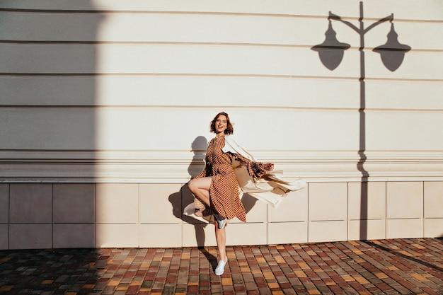 Portret van gemiddelde lengte van actief meisje dat in zonnige dag danst. buitenfoto van debonair gekrulde vrouw die op straat voor de gek houdt.