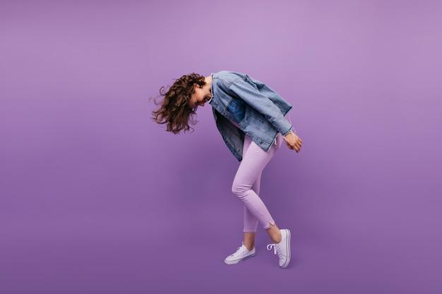 Portret van gemiddelde lengte van actieve modieuze vrouw. binnen schot van kaukasisch meisje met kort kapsel dansen.