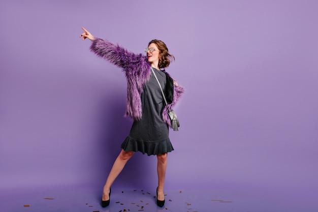 Portret van gemiddelde lengte van betoverende glamoureuze vrouw die in paars winterjasje danst
