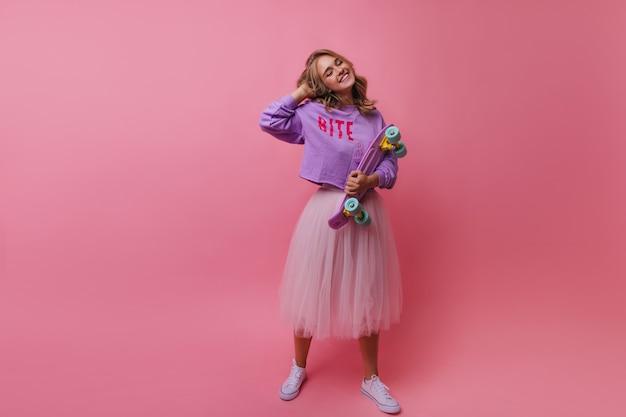 Portret van gemiddelde lengte van bevallig meisje in het lange weelderige skateboard van de rokholding. indoor portret van glimlachende romantische blonde vrouw met longboard.