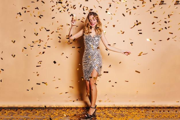 Portret van gemiddelde lengte van bevallige blonde vrouw in trendy kleding die op kerstmispartij koelen
