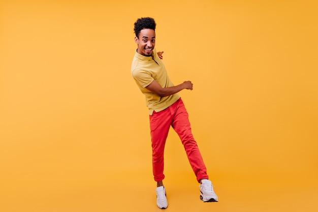 Portret van gemiddelde lengte van blije afrikaanse kerel in rode broek die voor de gek houdt. indoor foto van gekrulde zwarte man dansen.