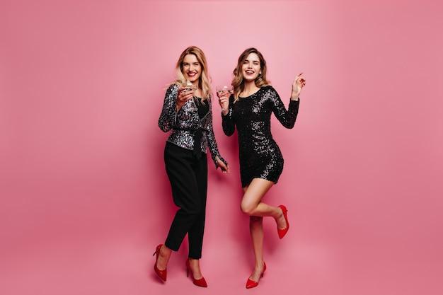 Portret van gemiddelde lengte van blije vrouw in fonkelingsjurk die op feestje koelen. het europese meisje van jocund in zwarte broek die zich voordeed op roze muur.