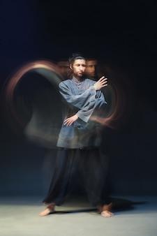 Portret van gemiddelde lengte van de mens in kimono die vechtsporten uitoefent op zwarte achtergrond met multiexposition