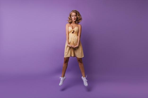 Portret van gemiddelde lengte van debonair europees meisje dat voor de gek houdt tijdens portretshoot. stijlvolle dame die in gele kleren op paars springt.