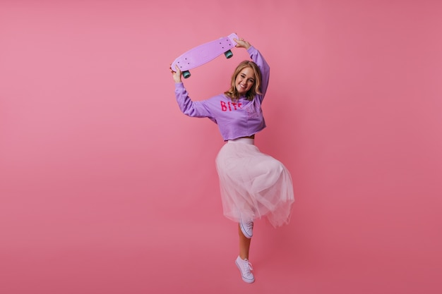 Portret van gemiddelde lengte van debonaire jonge dame die met skateboard ronddoolt. indoor portret van slank stijlvol meisje dansen op pastel.