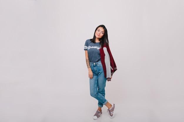 Portret van gemiddelde lengte van donkerharig vrouwelijk model in spijkerbroek. vrij donkerbruin meisje in jeans en trendy t-shirt poseren