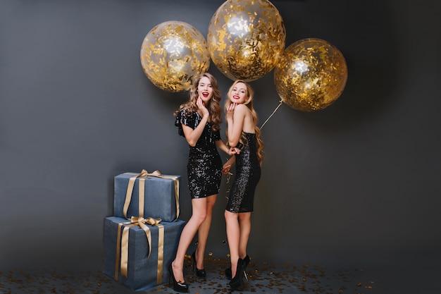 Portret van gemiddelde lengte van dromerig vrouwelijk model met de partijballons van de krullende kapselholding in haar ruimte. binnenfoto van blij meisje draagt zwarte jurk en staat in de buurt van blauwe geschenkdoos.