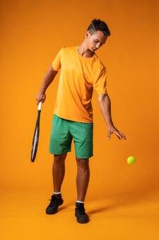 Portret van gemiddelde lengte van een man van de tennisspeler in actie tegen sinaasappel