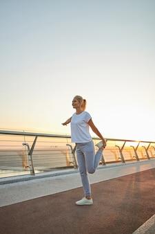 Portret van gemiddelde lengte van een tevreden vrouwelijke atleet die een staande quad doet op een voetgangersbrug foot