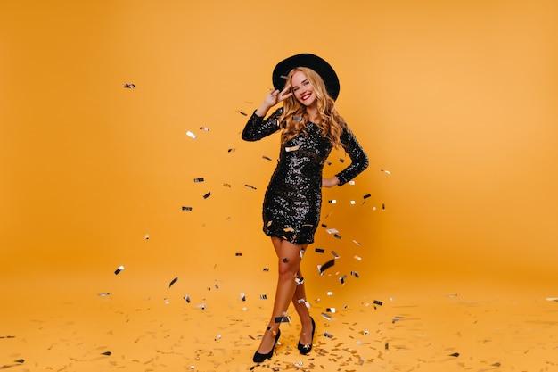 Portret van gemiddelde lengte van enthousiaste vrouw in grote zwarte hoed. opgewonden blond meisje dansen op gele muur.