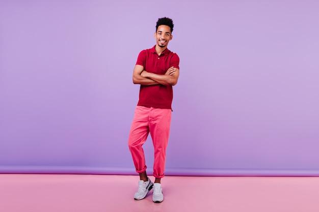 Portret van gemiddelde lengte van geïnteresseerd mannelijk model in roze broek. zorgeloze zwarte jonge man met gekruiste armen.