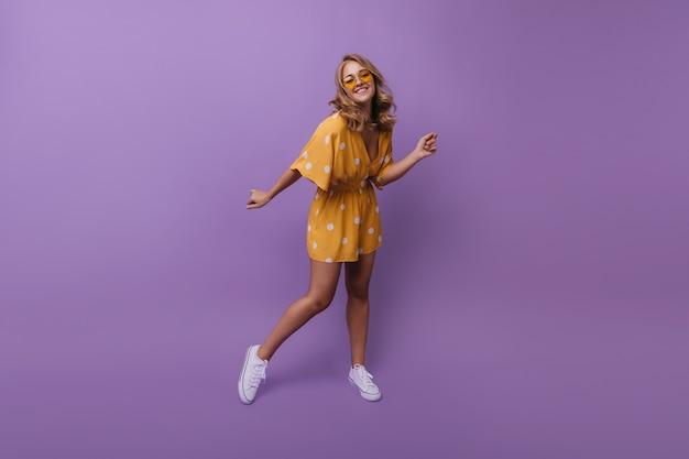 Portret van gemiddelde lengte van gelukkig gelooid meisje in witte sneakers. portret van tevreden blonde vrouw dansen tijdens portretshoot op paars.