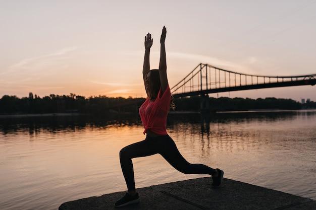 Portret van gemiddelde lengte van gelukkig slank meisje dat yoga op aard doet. buiten schot van tevreden dame genieten van training in de avond.