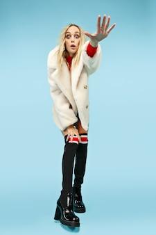 Portret van gemiddelde lengte van jonge elegante blonde grappige vrouw bij studio.