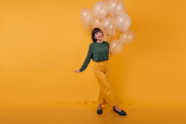 Portret van gemiddelde lengte van lachende vrouw met gekruiste benen. binnen schot van romantisch feestvarken dansen met gouden ballonnen.