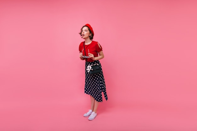 Portret van gemiddelde lengte van nieuwsgierig goed gekleed meisje met kort haar. elegante franse vrouw die verbazing uitdrukt.