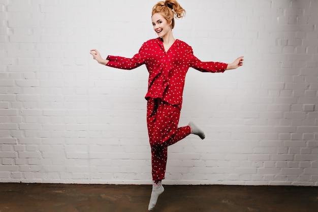 Portret van gemiddelde lengte van onbezorgd kaukasisch meisje dat in rode pyjama's op lichte muur danst schitterende jonge vrouw die in leuke nachtkleding met glimlach springt.